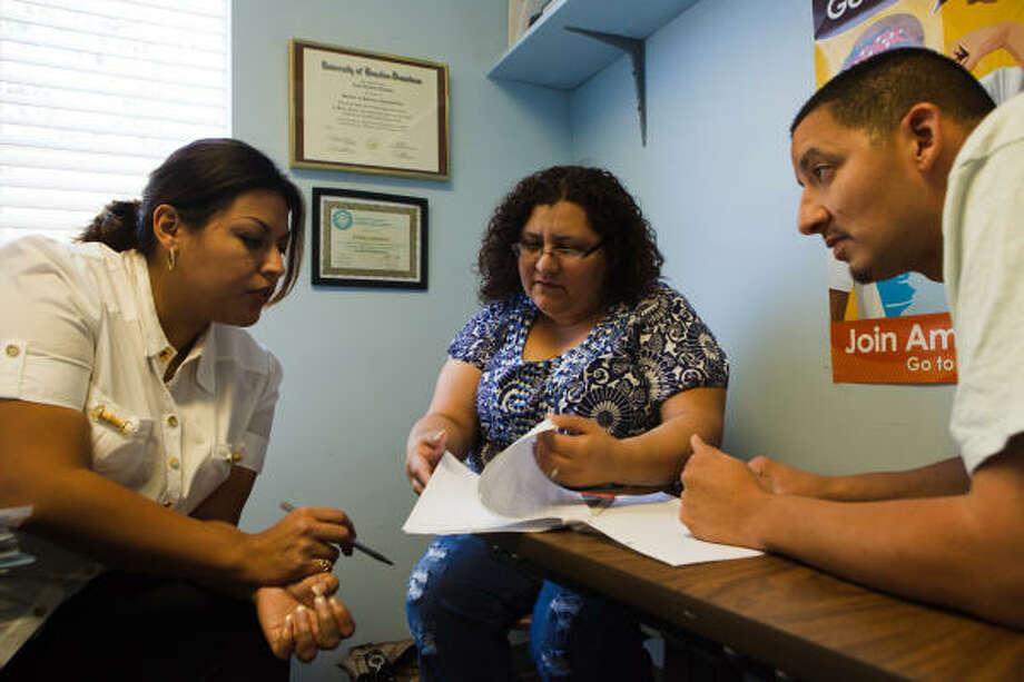 La asesora Erika Ledesma analiza el presupuesto de Richard y Esmeralda Contreras, quienes acuden al Centro de Oportunidades Financieras en el Wesley Community Center, en el Near Northside. Photo: Christopher Patronella, Jr., Para La Voz