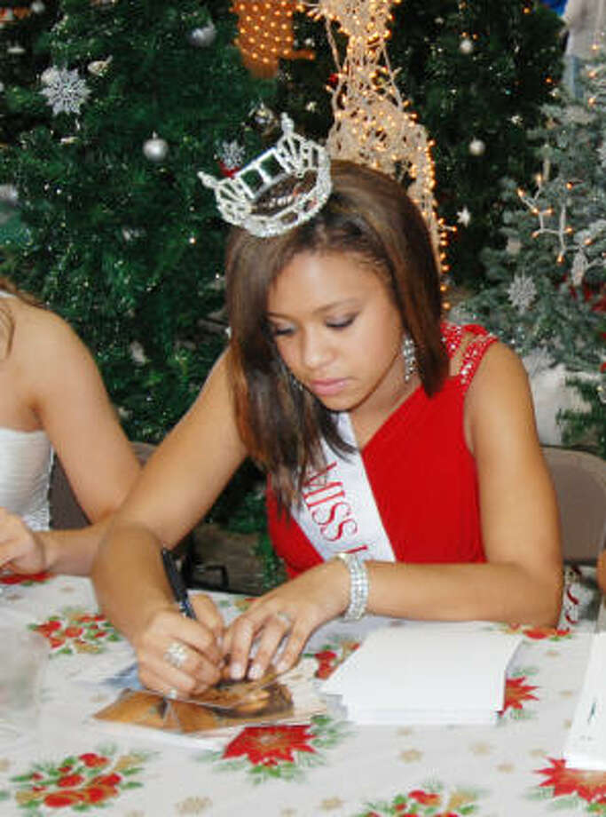 PHOTOS COURTESY OF MOOR FAMILY LOCAL WINNER: Jillyan Moor signs photos of herself while wearing the crown of Miss Teen Houston.