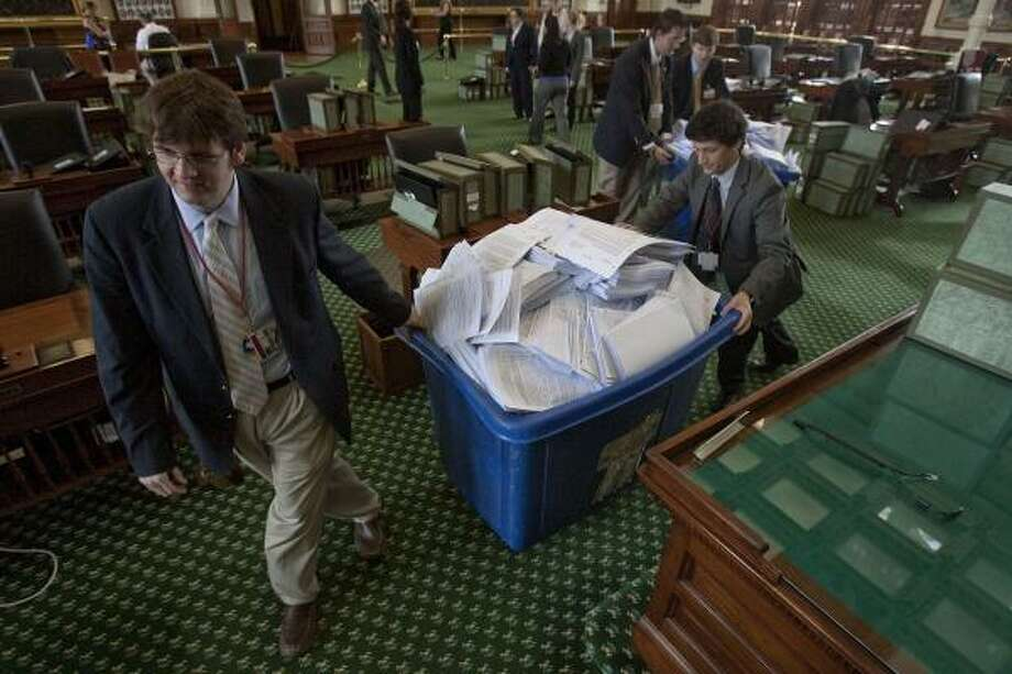 Daniel Brown, 27, left, and Edward Gooch, 22, right, of Austin, both assistant sergeant-at-arms of the Texas Senate, push a large recycling bin filled with bills and reports from senator desks from the 82nd legislative session in Austin on Tuesday. The reports and bills from the 82nd Session were recycled and cleared out to make room for the 30-day special session. The Senate reconvenes Thursday morning for hearings on education, finance and health care bills. Photo: Rodolfo Gonzalez, Austin American-Statesman