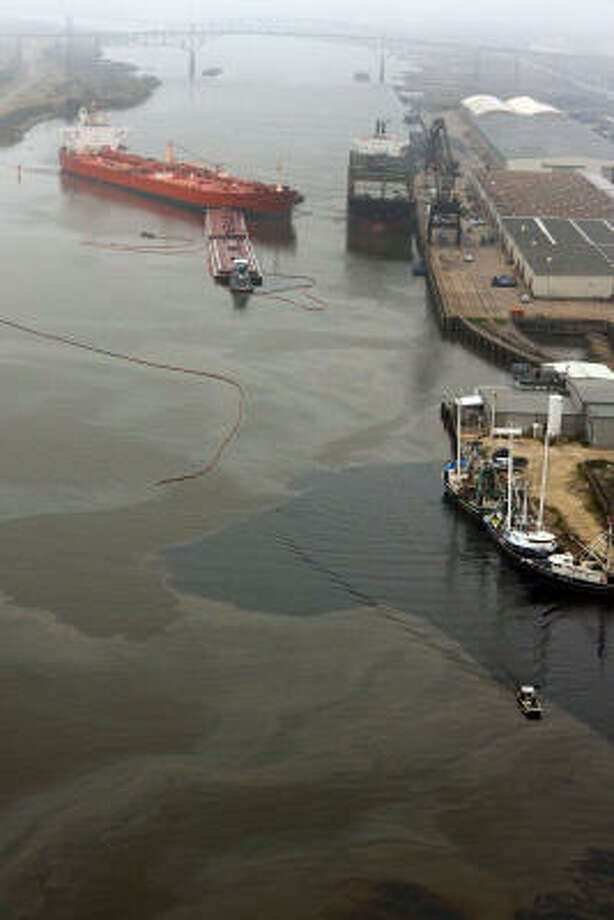 A barge and an oil tanker collided Jan. 23 in the Sabine-Neches Waterway, resulting in an oil spill. The 400-foot channel has not been widened since 1962, and pilots of huge vessels often must maneuver with sometimes only inches to spare. Photo: Julio Cortez, Chronicle