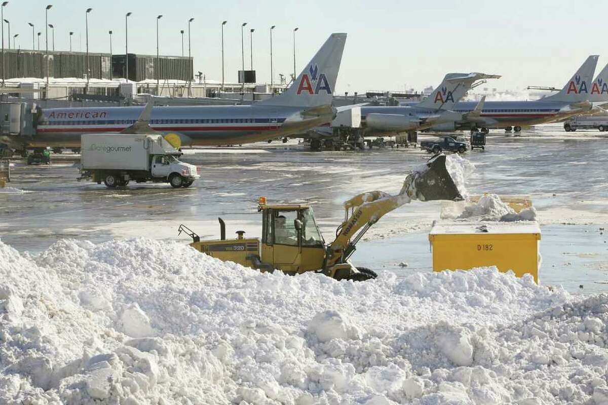 Workers remove snow from a runway at O'Hare International Airport February 3, 2011 in Chicago, Illinois. Commercial carriers at the airport started flying today for the first time since a blizzard forced the grounding of almost all planes Tuesday afternoon. Throughout the city residents continue to dig out from more than 20 inches of snow that fell on the area Tuesday and Wednesday.