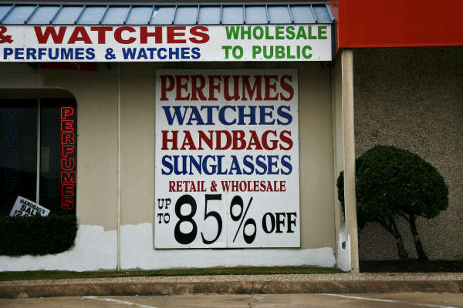 Coach has filed six lawsuits against retailers on Harwin Drive, where businesses like this one advertise discounts. In past suits, Coach has demanded $1 million per counterfeit item. Photo: Michael Paulsen, Chronicle
