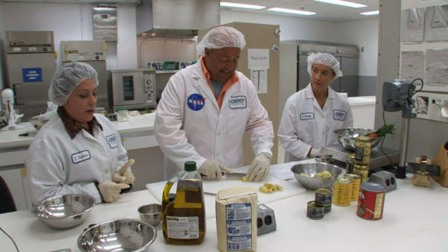 Andrew Zimmern, host of the Travel Channel's Bizarre Foods with Andrew Zimmern, chops an artichoke with NASA scientists at the Johnson Space Center. Photo: TRAVEL CHANNEL