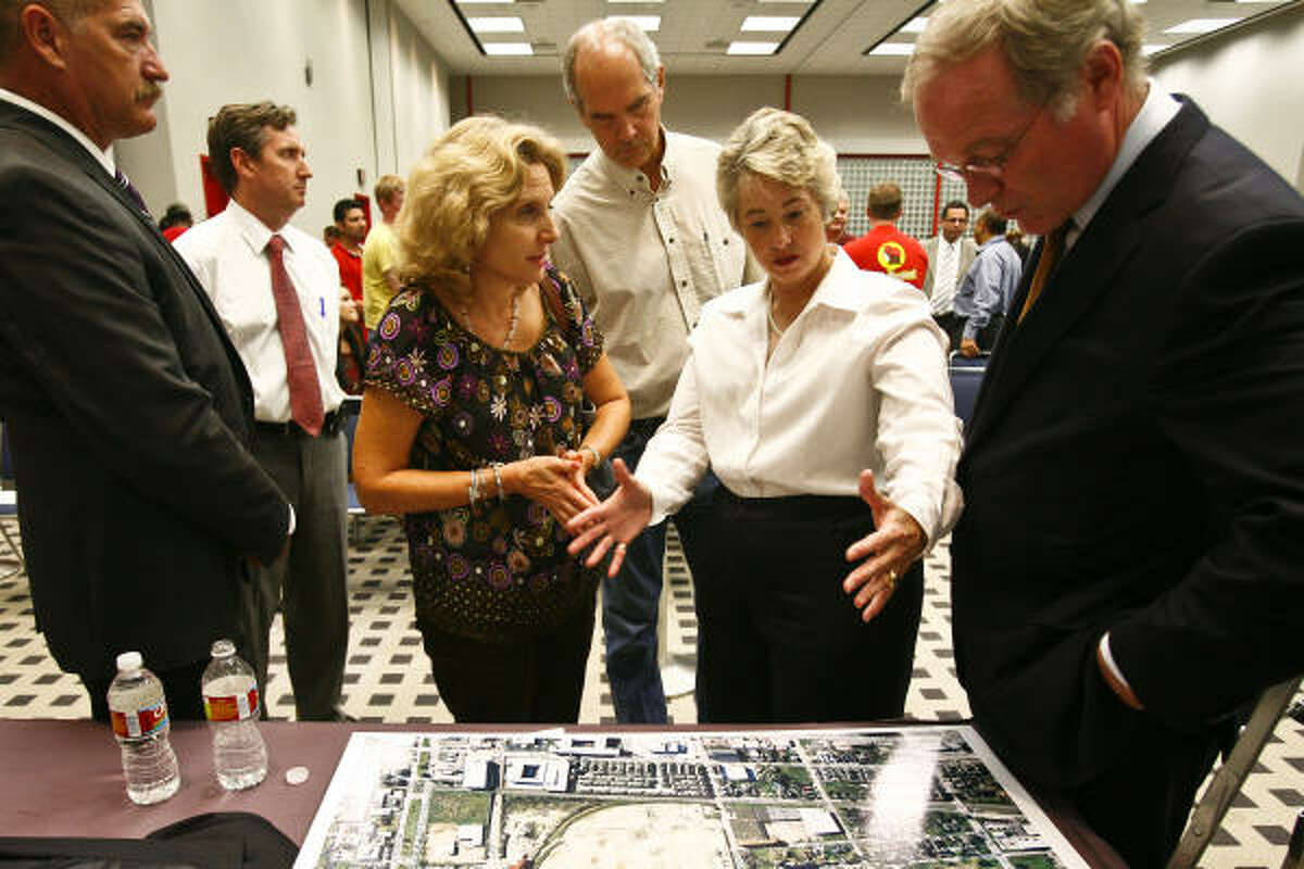 Mayor Annise Parker, second from right, talks with residents during Wednesday's public hearing scheduled to discuss plans for a proposed Heights Walmart.