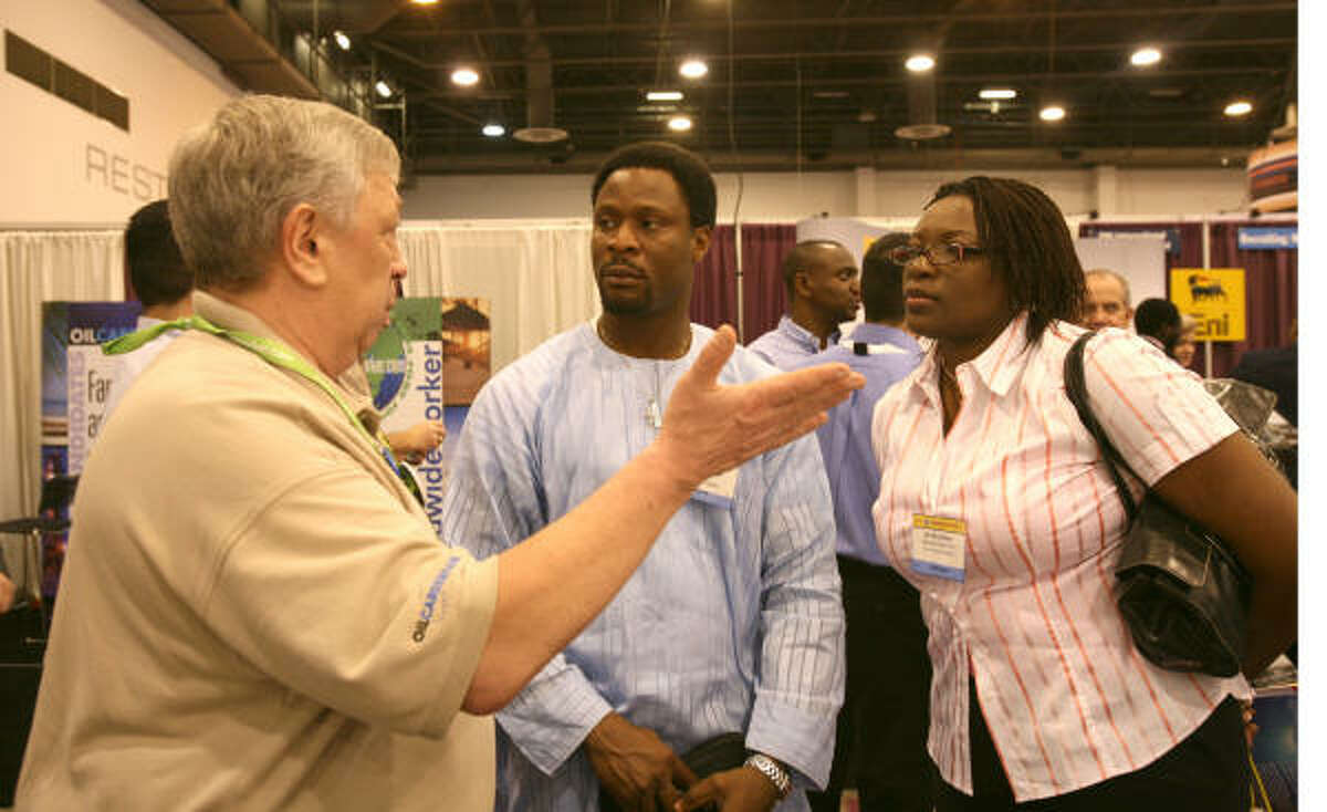 Bill French, left, executive search director with Worldwideworker.com, talks with James Omaruaye and Chidi Konkwo of Nigeria on Tuesday at the Offshore Technology Conference. ``Companies are having to get creative'' to find new employees, French said.
