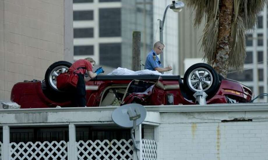 The driver was killed when a car fell 41 feet and landed wheels up on a downtown building's roof, a Houston fire official said. Photo: BRETT COOMER, CHRONICLE
