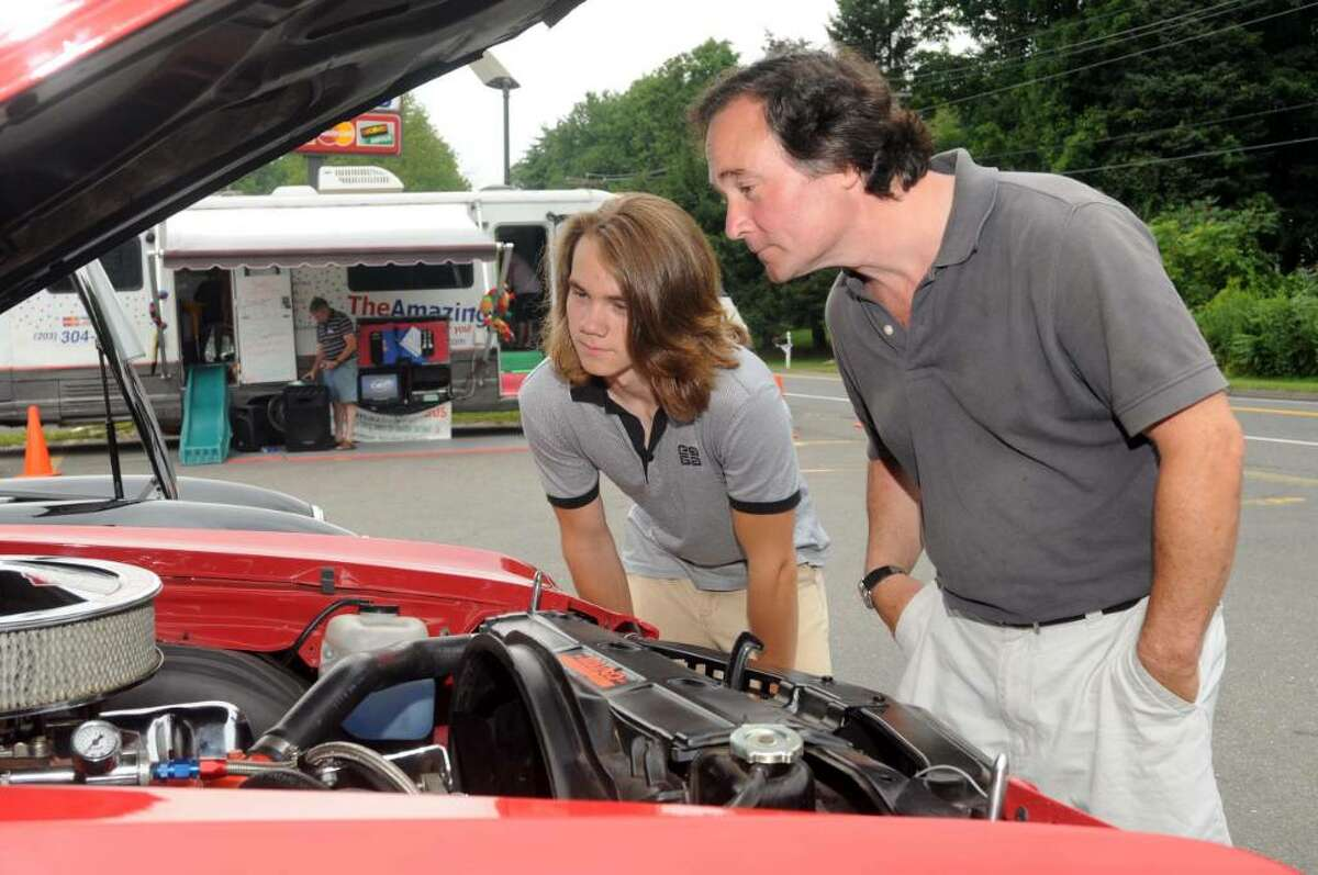 The Dodgingtown Market's annual car show was held Sunday in Newtown. Proceeds from the show, and profits from the market during the show, are donated to U.S. soldiers serving abroad and to breast cancer research. Max Schmitt, 15, and his father, Chris Schmitt, both of Newtown, check out the engine of a Chevy Chevell Super Sport.
