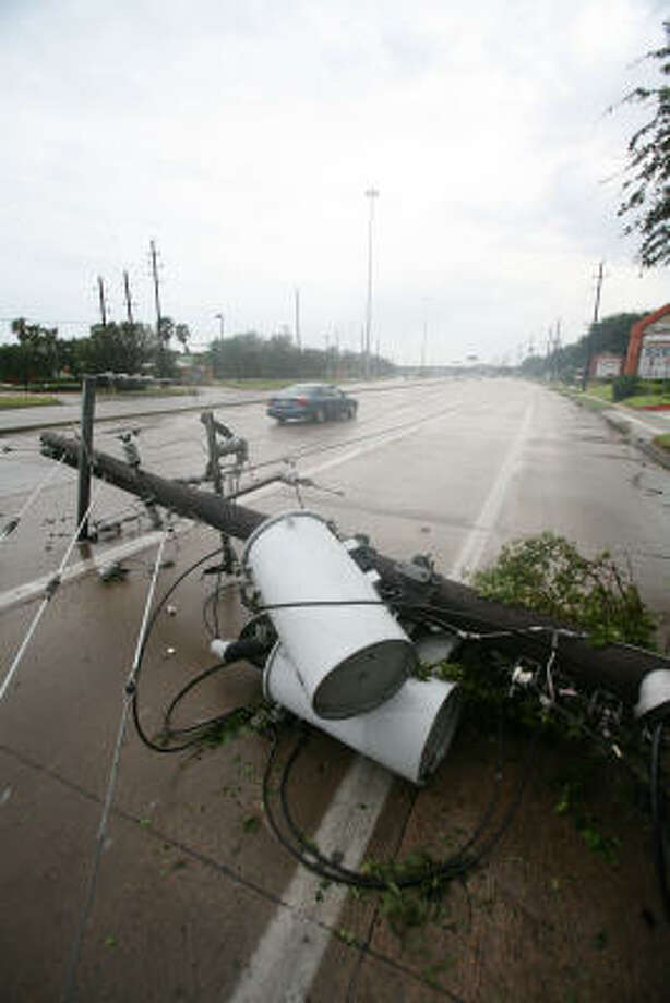 A utility pole with transformers blocks lanes on FM 1960 in the wake of Hurricane Ike. Photo: STEVE CAMPBELL, Chronicle