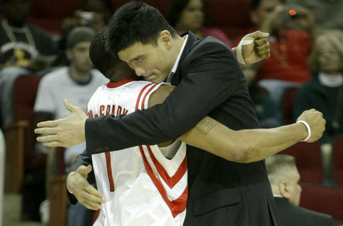 Sidelined Rockets center Yao Ming, right, embraces his teammate Tracy McGrady.