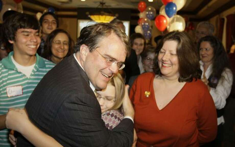 Caroline Culberson, 12, hugs her father, U.S. Rep John Culberson, as her mother, Belinda, watches at a party at Maggiano's. Photo: MELISSA PHILLIP, CHRONICLE