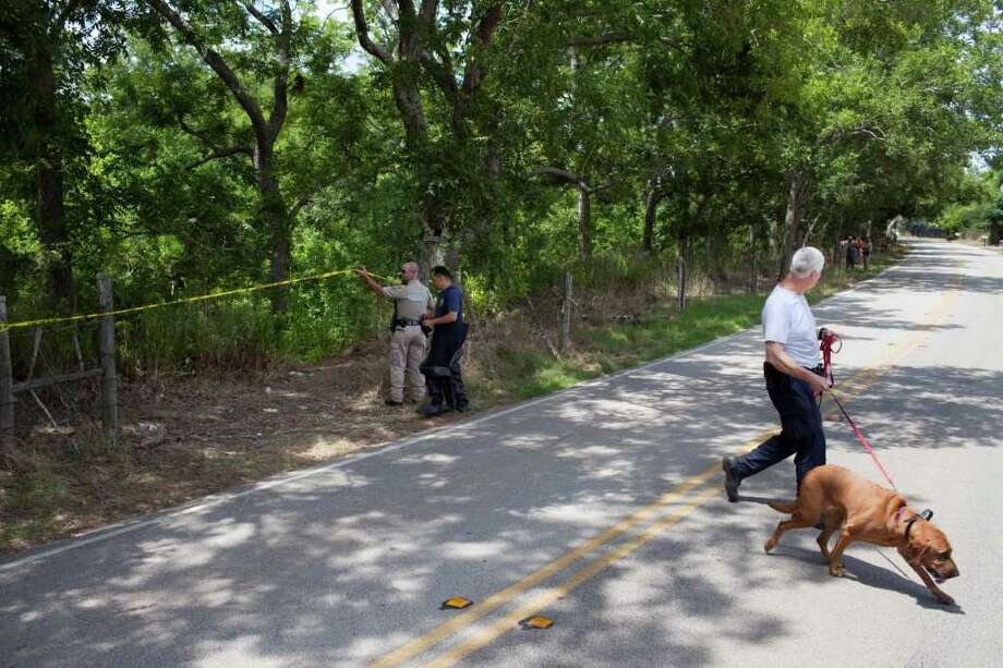 A HPD K-9 officer and bloodhound leave the scene where Houston and Fort Bend county authorities search for the remains of Laura Jean Ackerson, July 24, 2011 in Oyster Creek off of Skinner Rd. in Fort Bend county, Texas. Two people, Grant Ruffin Hayes and wife Amanda Perry Hayes, have been arrested in connection to the case. Body parts alleged to be Ackerson's have been found in the creek. Photo: Eric Kayne / © 2011 Eric Kayne