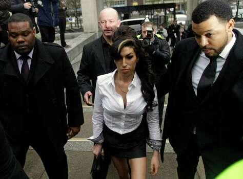 FILE - In this Jan. 20, 2010 file photo, British singer Amy Winehouse, center, arrives at Magistrates Court in Milton Keynes, England. Winehouse, the beehived soul-jazz diva whose self-destructive habits overshadowed a distinctive musical talent, was found dead Saturday, July 23, 2011, in her London home, police said. She was 27.   (AP Photo/Matt Dunham, File) Photo: Matt Dunham, STF / AP