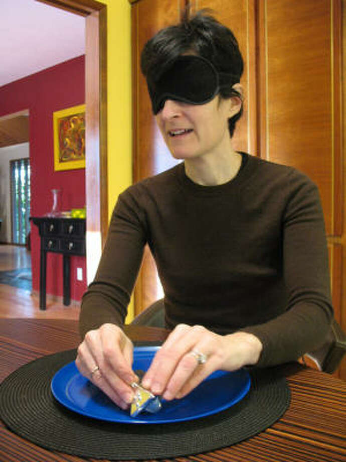 Jewish artist Marsha Plafkin Hurwitz wears a blindfold while playing with the Braidel, a dreidel she created with Braille letters. Photo: NICOLE NEROULIAS:, RELIGION NEWS SERVICE