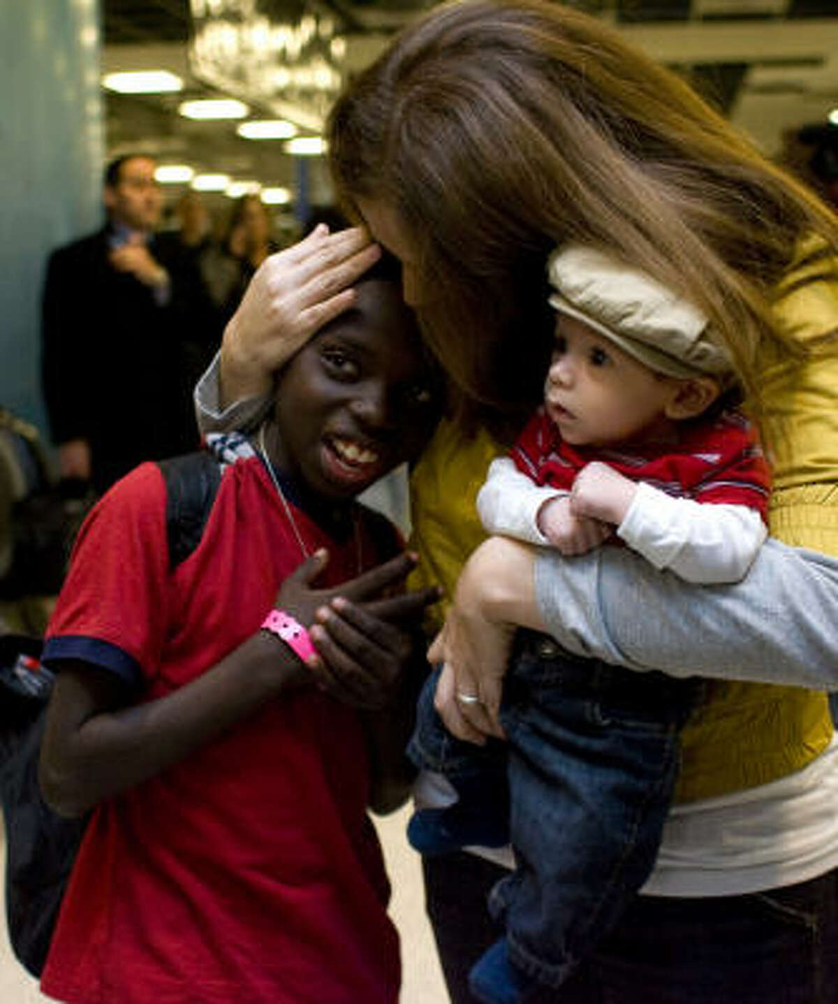 Holding her 6-week-old, Jude, Debra Parker hugs Ronel, 9, who arrived from Haiti on Thursday with his dad, Ernest Parker. New sister Carly, 12, and brother Colton, 10, were at the airport, too.