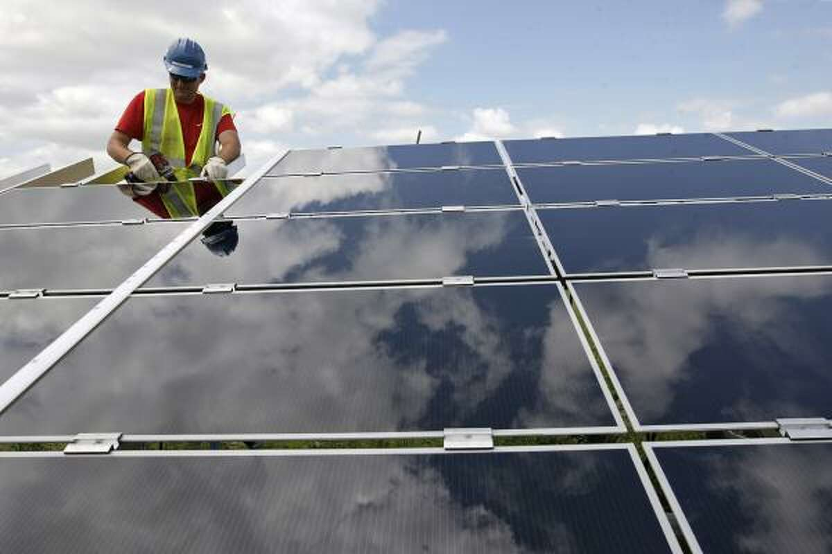 Jared Anderson works on a solar panel as the Blue Wing solar farm prepares to open. Statewide, at least six more projects are in development.