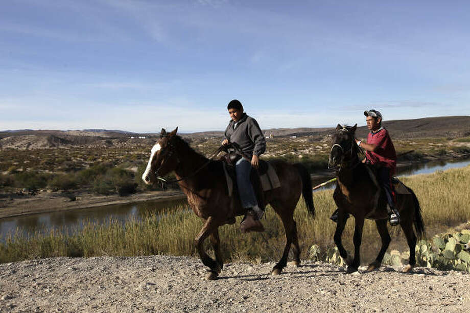 Children on horseback ride Thursday along the Rio Grande at Boquillas Del Carmen. Construction at a border crossing in the area will begin this summer. Photo: Jerry Lara, San Antonio Express-News