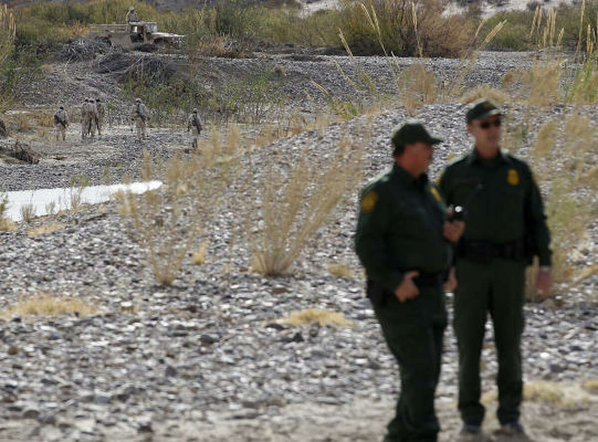 Mexican army personnel patrol their side of the Rio Grande at Boquillas Del Carmen on Thursday as U.S. Border Patrol agents stand guard. Customs and Border Protection Commissioner Alan Bersin visited the area.