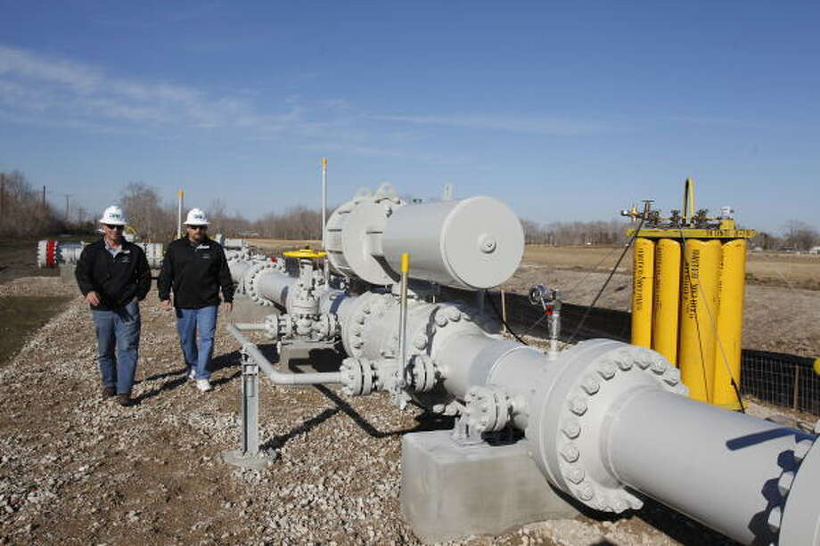Denbury Resources employees Alvaro J. Parra, left, and Randy Robichaux inspect one of the pipelines in Alvin near the historic Hastings field, which was discovered in 1934 and has produced about 600 million barrels of oil over its lifetime. Photo: Melissa Phillip, Chronicle