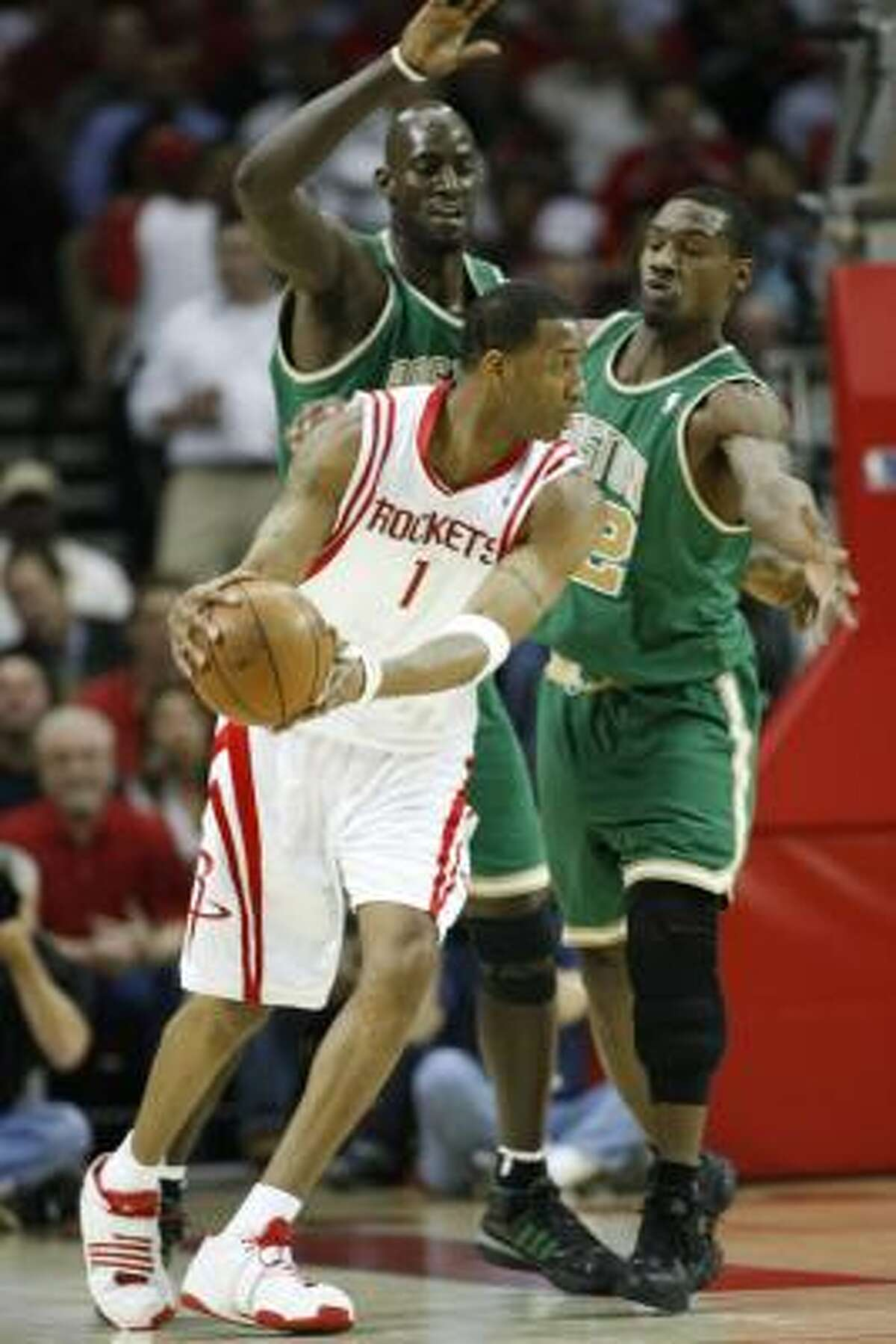 Rockets guard Tracy McGrady looks to pass as Boston's Kevin Garnett (5) and Tony Allen defend