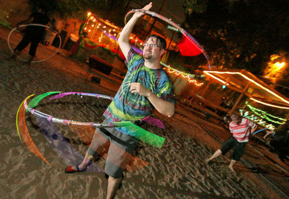 Fabienne Jones-Sotunde, from left, Patrick Spong and Jason Dorn practice their Hula Hooping technique at Last Concert Cafe in preperation for World Hooping Day. Photo: Bill Olive, For The Chronicle