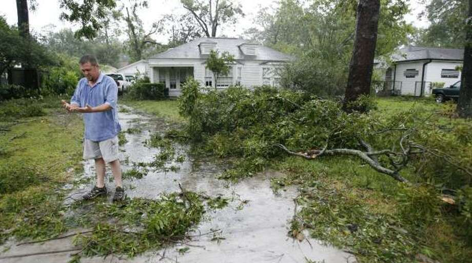 Paul Kopecky wipes his hands off after clearing tree limbs brought down by Hurricane Ike from a residence in Garden Oaks. Photo: KAREN WARREN, CHRONICLE