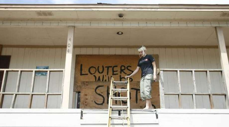Ashli Pingry, 19, of Oak Island, has a stern warning for any would-be looters. Photo: SHARÓN STEINMANN, CHRONICLE