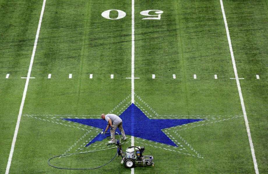 Dallas Cowboys field supervisor Chris Morrow paints the star on the 50-yard line at the Alamodome on Monday, July 25, 2011, in preparation of the team beginning its annual training camp in San Antonio on Thursday. Photo: Edward A. Ornelas/eaornelas@express-news.net / SAN ANTONIO EXPRESS-NEWS NFS