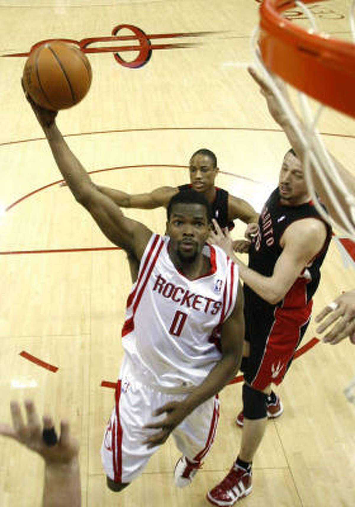 Rockets guard Aaron Brooks drives to the basket past Hedo Turkoglu, right.