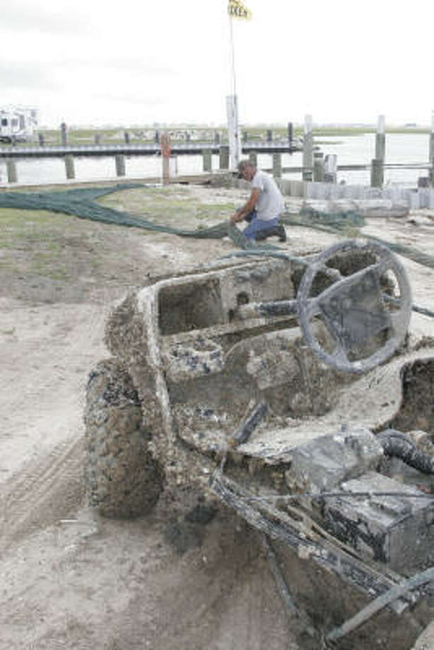 """Tim Perkins works to repair damage to a shrimp trawl torn when the net caught the all-terrain vehicle in the foreground while being pulled in Lower Galveston Bay this past week. The barnacle- and oyster-encrusted ATV was one of two of the vehicle's shrimpers based at Stingaree Marina on Bolivar Peninsula """"caught"""" this past week. Despite determined and efficient work by Texas General Land Office, scattered debris washed into the bay by Hurricane Ike still sits on the bay bottom. Photo: Shannon Tompkins, Chronicle"""