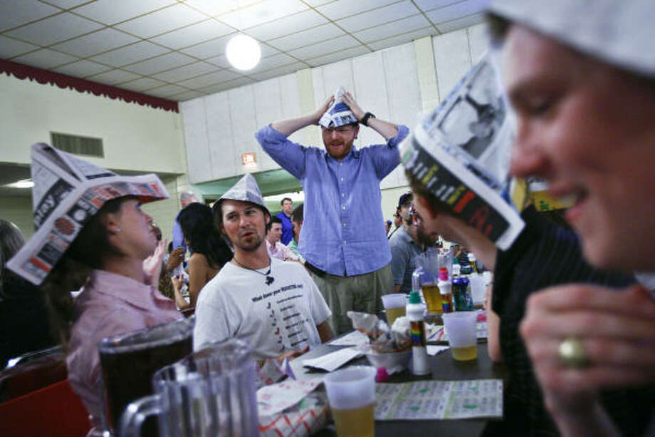 Efaw, left, and Gavin MacPherson laugh with friends after building paper hats during the weekly bingo game at the SPJST Lodge #88 in the Heights. The senior citizens are now sharing their bingo nights with young professionals in their 20s and 30s. Photo: Michael Paulsen, Chronicle