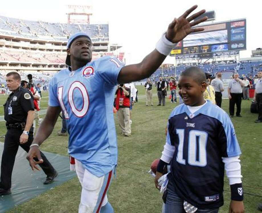 Vince Young, shown with Tyler McNair, a son of Steve McNair, has re-introduced himself to Titans fans. Photo: Wade Payne, AP