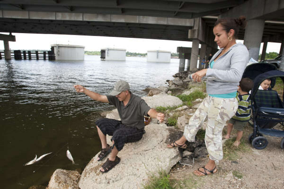 Giovani Pimale and Sandra Casto fish near the I-10 bridge that spans the San Jacinto River at Crosby-Lynchburg Road. The river in that area is polluted with dioxins, chemicals so toxic that they're measured in trillionths of a gram.
