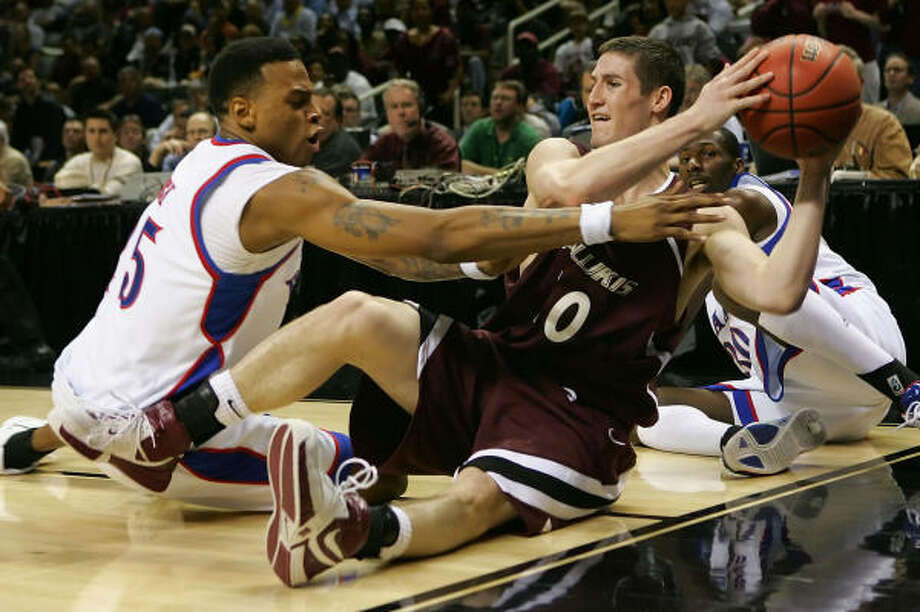 Southern Illinois' Bryan Mullins (10) looks to pass under pressure from Kansas' Brandon Rush (35) during Thursday's West Regional game at San Jose, Calif. The Jayhawks won 61-58. Photo: Lisa Blumenfeld, Getty Images
