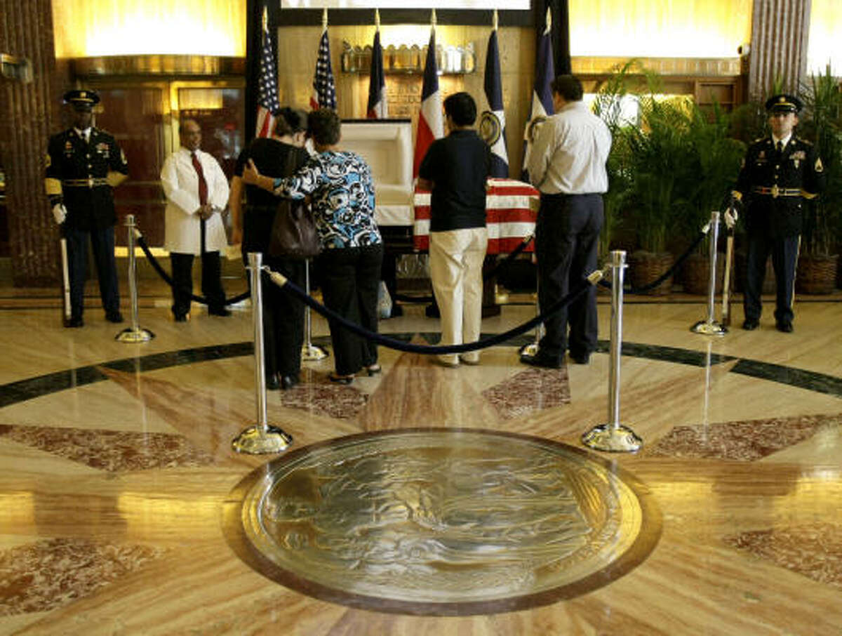 Karen Lawson, left, and Virginia Rodriguez, right, both of whom knew Dr. Michael DeBakey from working at Baylor College of Medicine, embrace as they stand beside the heart surgeon's casket in the rotunda of Houston City Hall.