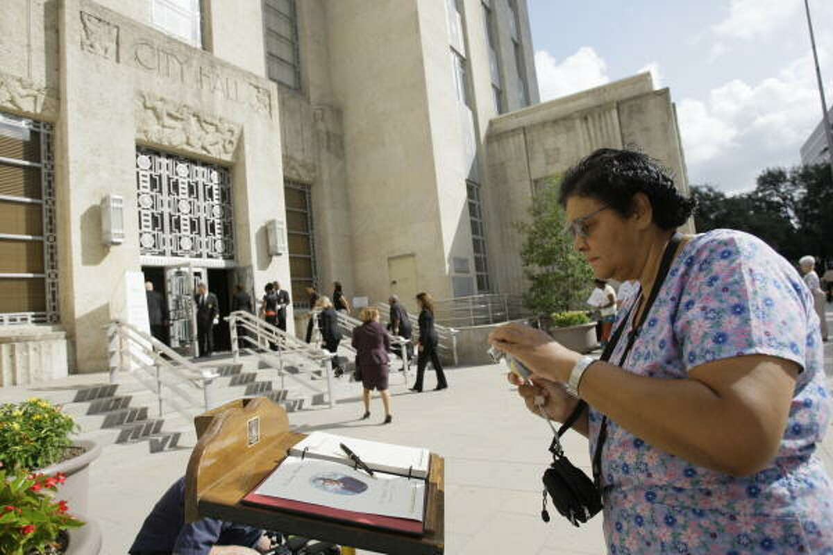 Veronica Coulson, a nurse at Texas Children's hospital, takes a photo after sign the condolence book outside city hall where Dr. Michael DeBakey is lying in repose at the rotunda.