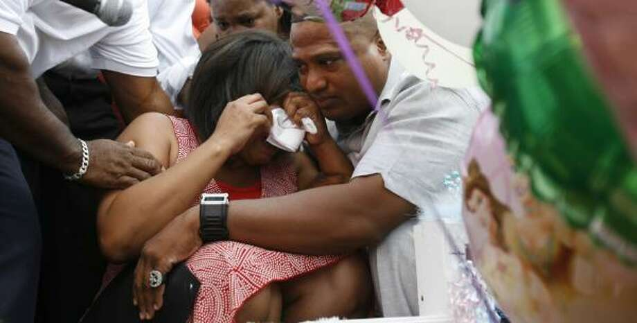 At Sunday evening's vigil, Quanell X embraces Jerilynn St. Cyr, the mother of the two children. Photo: SHARÓN STEINMANN, CHRONICLE