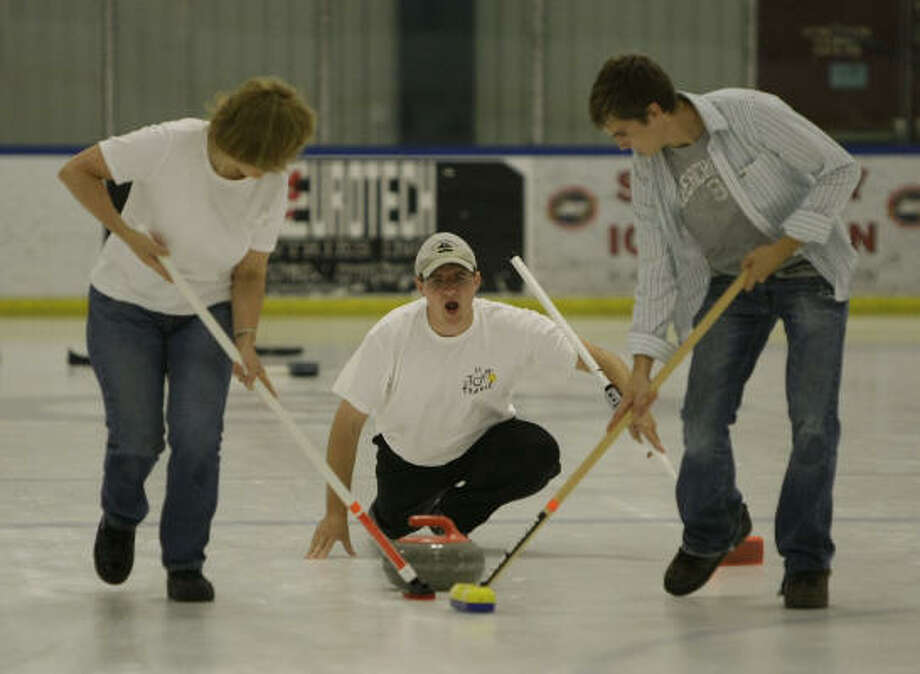 Dan Ostheimer, center, yells as he releases the rock into the care of sweepers Patricia Obara and Tyler Drummond during a game at the Learn to Curl class at Space City Ice Station. Photo: Karen Warren, Houston Chronicle