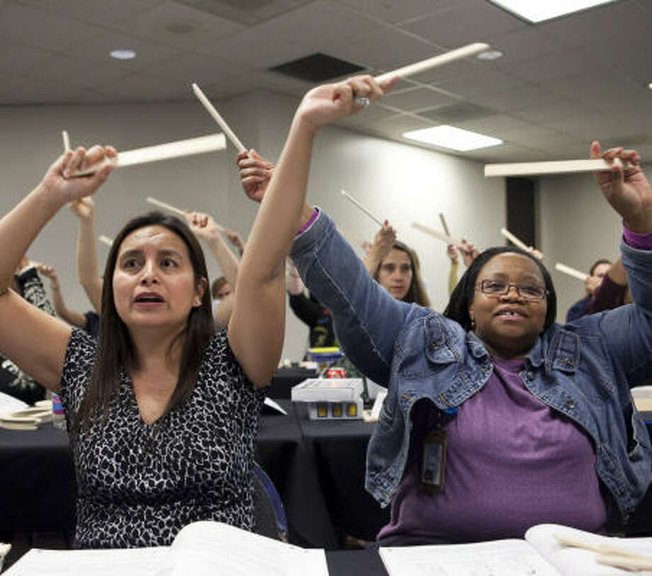 """Pre-kindergarten teachers Gloria Garcia, left, and LaShanda Richards participate in a counting exercise Friday evening during a """"Handwriting Without Tears"""" training session. Garcia came from Edingburg, and Richards teaches at The Rice School. Photo: Nathan Lindstrom, Chronicle"""