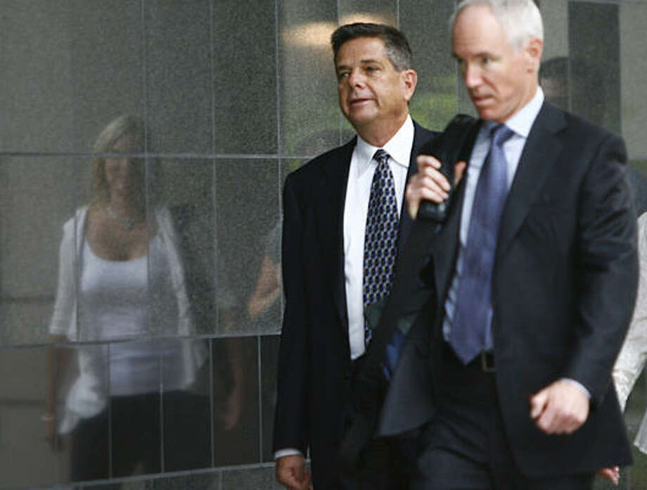 Joe Hirko, left, a former head of Enron's broadband unit, walks to the Bob Casey Federal Courthouse Monday. Besides prison time, Hirko must pay millions in restitution. Photo: Mayra Beltran, Chronicle