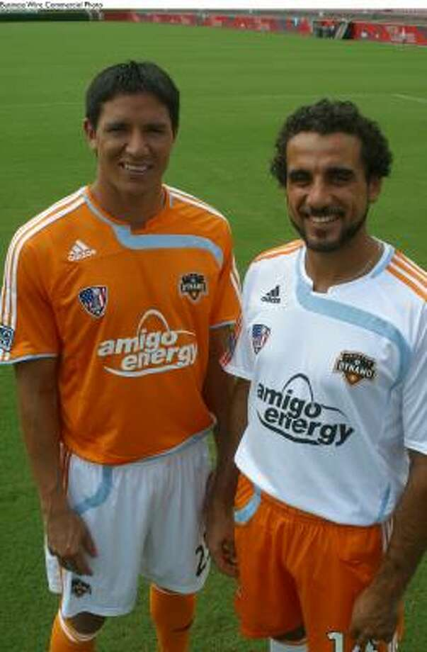 Brian Ching, left, and Dwayne De Rosario model new jerseys displaying the Amigo Energy logo, the team's official jersey sponsor. The Dynamo will take the field with their new look for the first time at Sunday's home game against FC Dallas. Photo: BUSINESS WIRE