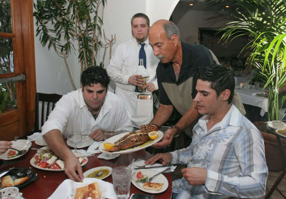 Frixos Hrisinis, third from left, serves whole red snapper to customers Jimmy Halastaras, left, and his brother, Stavros Halastaras. Photo: Gary Fountain, For The Chronicle