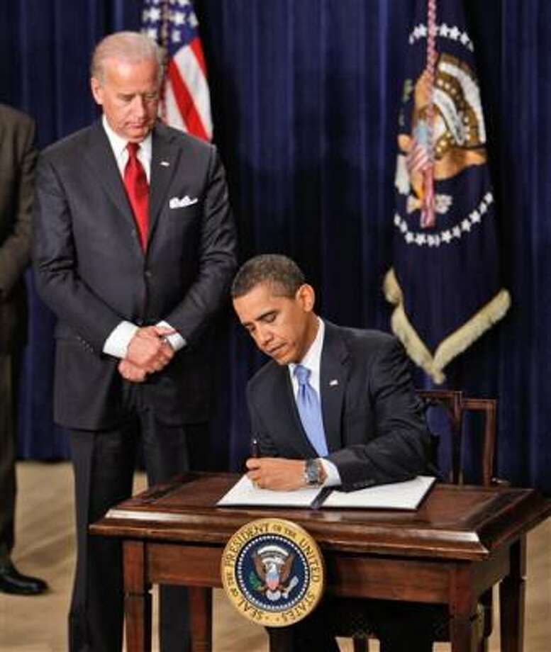 President Barack Obama signs a series of executive orders, including one closing of the prison at Guantanamo Bay, Thursday in the Oval Office of the White House in Washington. Photo: Charles Dharapak, AP
