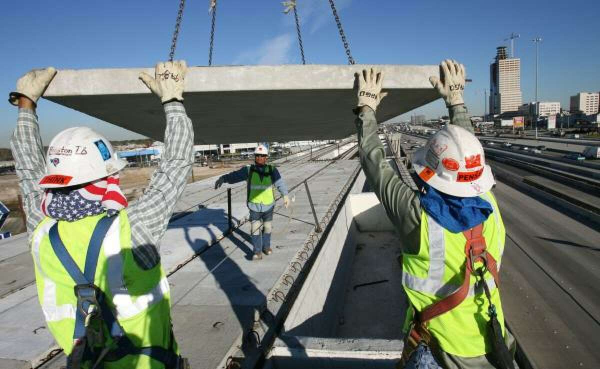 Workers maneuver material on the Katy Freeway. The project is winding up ahead of schedule. The expansion is