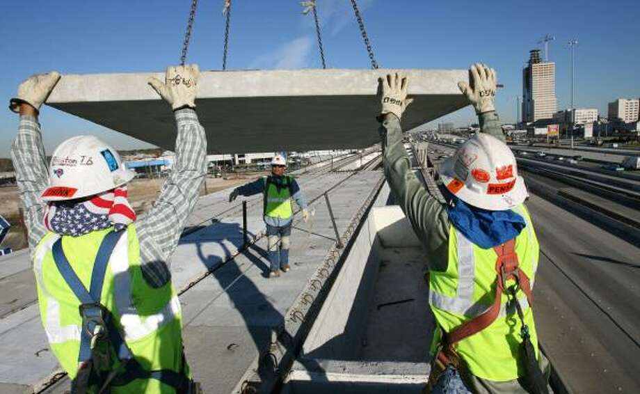 "Workers maneuver material on the Katy Freeway. The project is winding up ahead of schedule. The expansion is ""like giving west Houston a quadruple bypass,"" U.S. Rep. John Culberson says. Photo: SHARÓN STEINMANN, CHRONICLE"