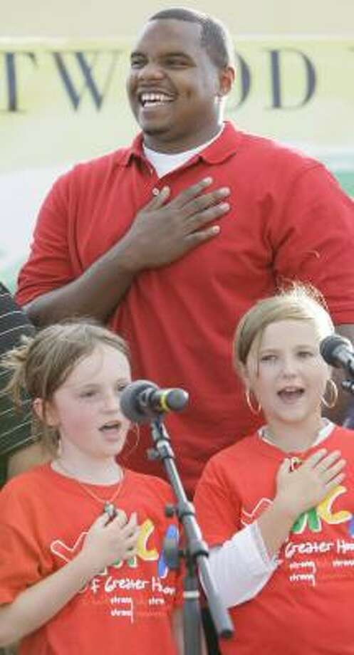 Chester Pitts joins Murphy Baker, 9, left, and Haley Brockway, 10, of the South Montgomery County YMCA performing arts program onstage during the national anthem. Photo: MELISSA PHILLIP, CHRONICLE