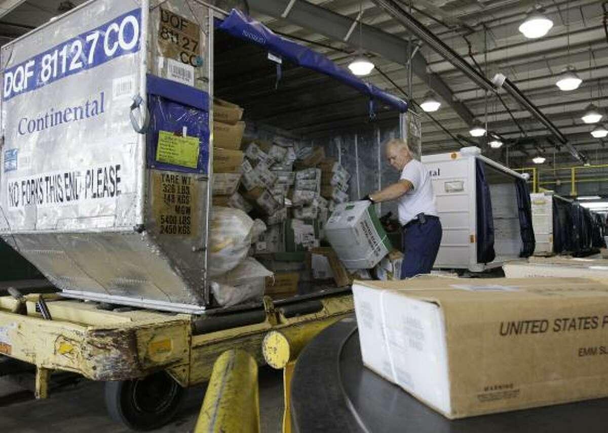 Cargo agent Mark Zalar unloads mail at Continental's facility at Bush Intercontinental Airport.