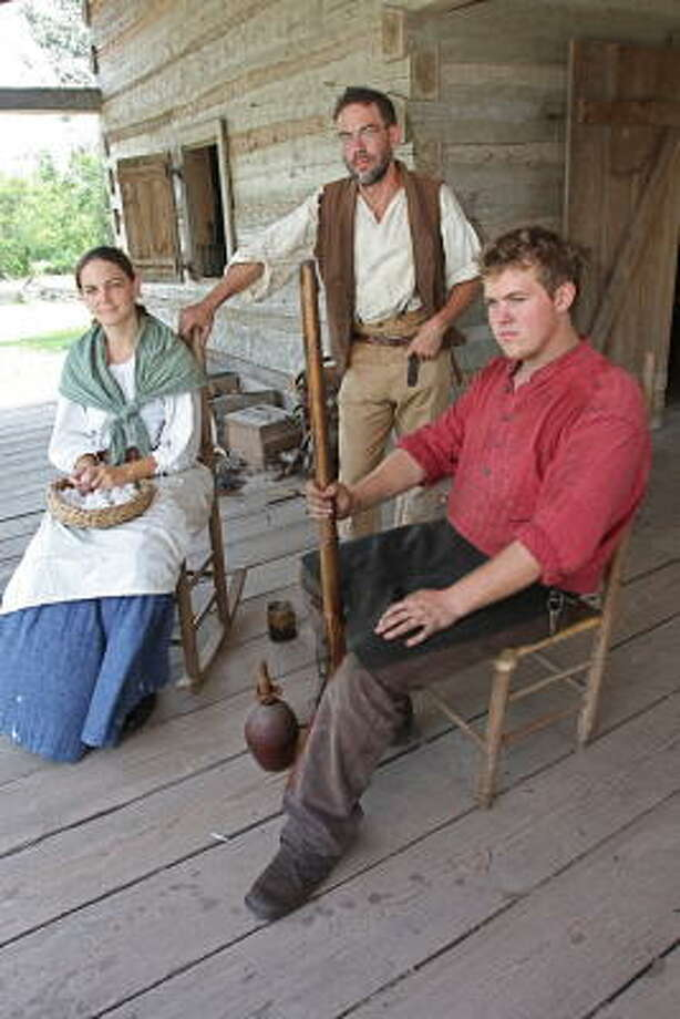 J.R. Thomas of Sugar Land, second from left, portrays Farmer Jones at the 1830 log house at the George Ranch Historical Park. He would like to see more people volunteer to work at the ranch. With him, from left, are: Leslee Gupton, 25, of Richmond as Nancy Jones and Lukas Smith, 20, of Wharton as the blacksmith. Photo: Suzanne Rehak, For The Chronicle
