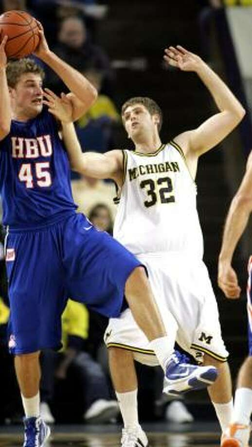 Houston Baptist center Mario Flaherty (45) tries to pass the ball while being defended by Michigan forward Zack Gibson (32). Photo: Tony Ding, AP