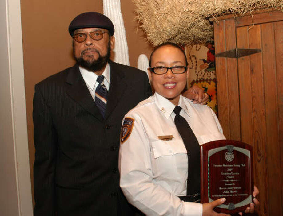 HIGHEST HONOR: Harris County Sheriff's department Detention Officer Julia Harris,right, and her father Joe Harris,left, hold her Hero of the Year Award presented by Westchase Rotary Club. Photo: For The Chronicle George Wong