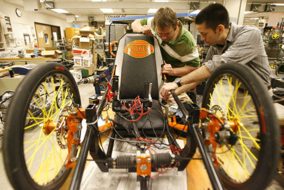 Ceasar Nunez, 25, right, and Nathan Davis, 27, mechanical engineering and technology seniors, tweak one of two UH entries for this weekend's Shell Eco-marathon in Houston. Photo: Julio Cortez, Chronicle